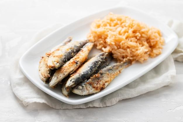 Gebratene kleine sardinen mit tomatenreis auf weißem teller auf keramikhintergrund