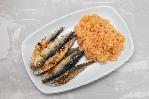 Gebratene kleine sardinen mit tomatenreis auf weißer schale auf keramiktisch