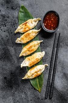 Gebratene knödel. chinesisches essen kochen. schwarzer hintergrund. draufsicht.