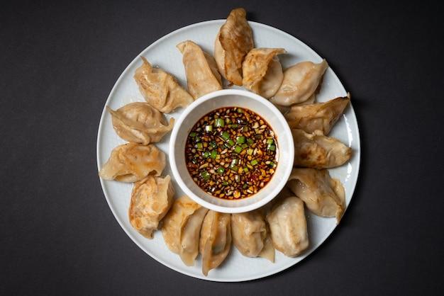 Gebratene knödel im gyoza-stil in einem teller mit würziger sojasauce auf schwarzem hintergrund. asiatisches essen zum mitnehmen.