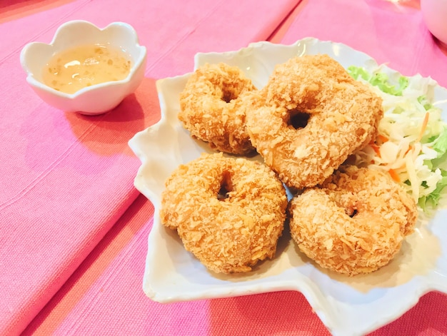 Gebratene knusperige hühnernuggets mit hühnersoße und frischgemüse in der weißen platte.