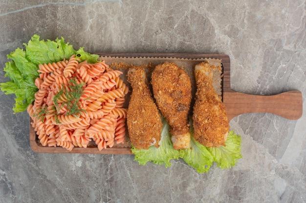 Gebratene knusprige chicken nuggets mit leckeren makkaroni auf holzbrett.