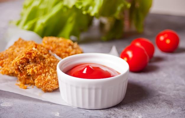 Gebratene knusprige hühnernuggets mit ketchup-sauce