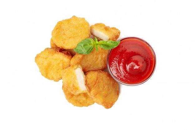 Gebratene knusprige hühnernuggets und ketchup isoliert