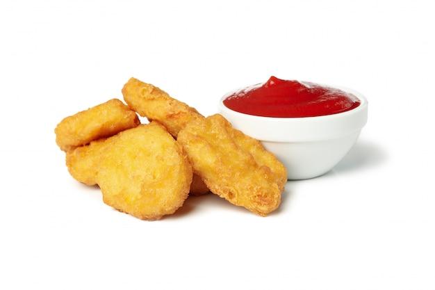 Gebratene knusprige hühnernuggets und ketchup lokalisiert auf weißem hintergrund