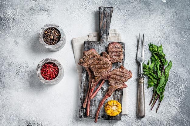 Gebratene koteletts steaks von lamm hammelfleisch auf einem holzbrett. weißer hintergrund. ansicht von oben.