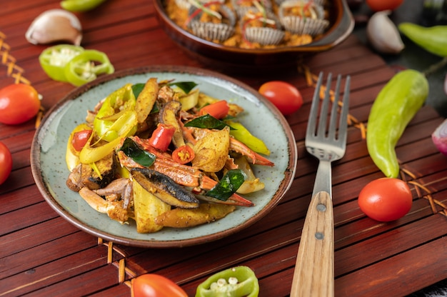 Gebratene krabben mit currypulver in einem teller mit paprika und tomaten.