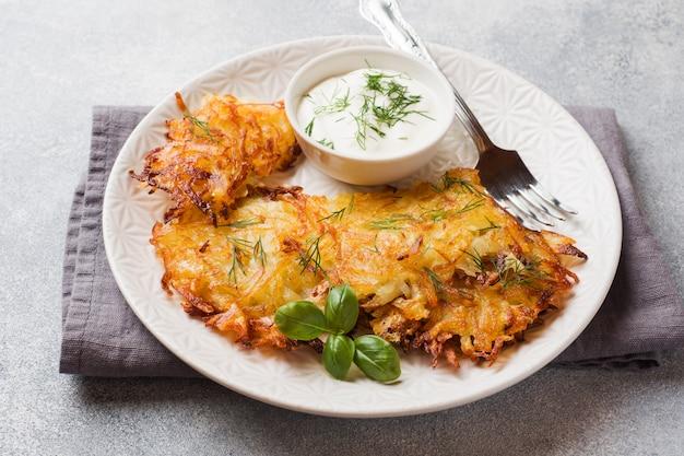 Gebratene kuchen von geriebenen kartoffeln auf der platte mit soße. boxty raggmunk der traditionellen pfannkuchen