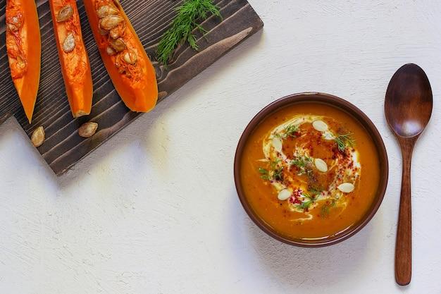Gebratene kürbis-möhren-suppe mit sahne, schwarzem pfeffer und kürbiskernen, schneidebrett und frischen kürbisscheiben, schwarzbrot