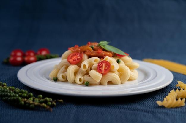 Gebratene makkaroni mit tomaten, chili, pfeffersamen und basilikum in einer weißen schale.