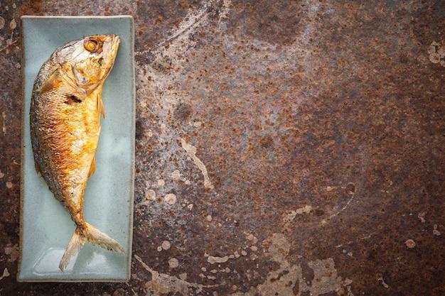 Gebratene makrele in rechteckiger keramikplatte auf rostigem texturhintergrund mit kopienraum für text, draufsicht