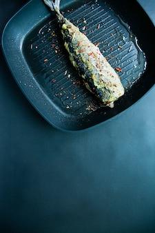 Gebratene makrelen in einer grillpfanne. dunkler hintergrund. platz für teskta.