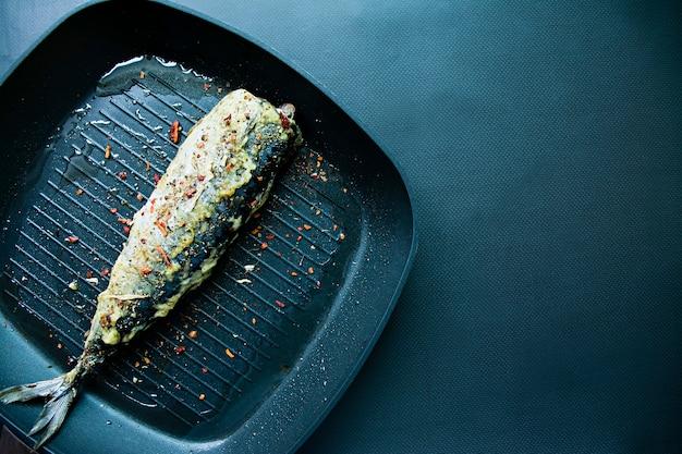 Gebratene makrelen in einer grillpfanne. dunkler hintergrund.
