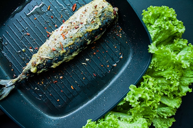 Gebratene makrelen in einer grillpfanne. richtige ernährung. dunkler hintergrund.