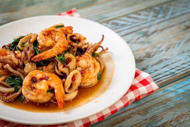 Gebratene meeresfrüchte (garnelen und tintenfisch) mit thai-basilikum - asiatische küche