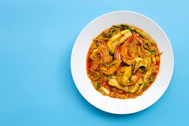 Gebratene meeresfrüchte mit currypulver auf blauem hintergrund