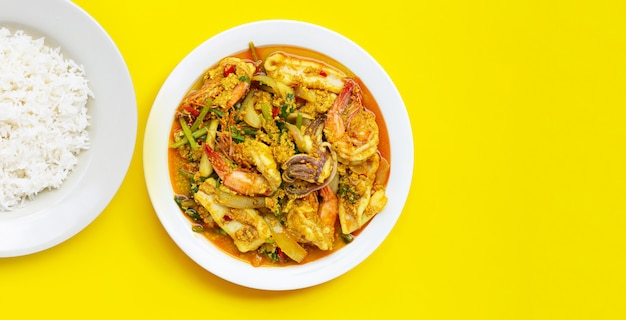 Gebratene meeresfrüchte mit currypulver mit reisschale auf gelbem hintergrund.