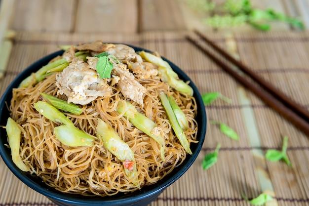 Gebratene nudel mit dem appetitanregenden schweinefleisch, das auf den speisetisch gesetzt wird.