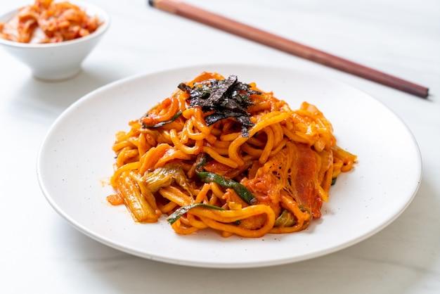 Gebratene nudeln mit koreanischer würziger sauce und gemüse umrühren