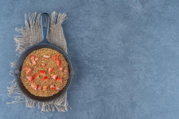 Gebratene nudeln mit tomatenscheiben auf schwarzer pfanne.