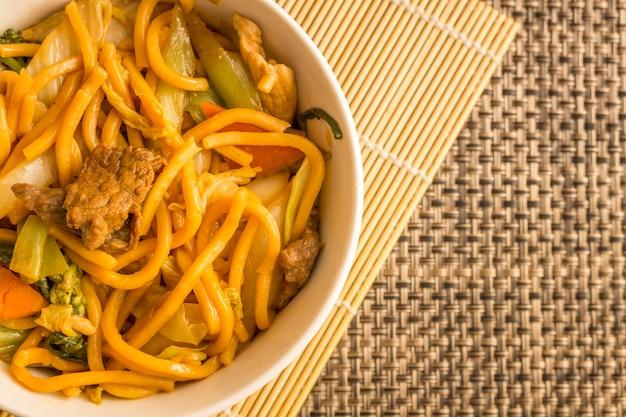 Gebratene nudeln. yakisoba mit rindfleisch, huhn und gemüse in einer weißen schüssel.