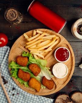 Gebratene nuggets mit pommes-frites auf hölzernem brett