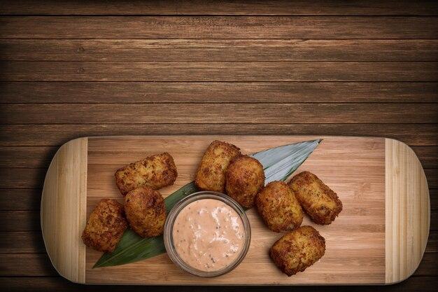 Gebratene nuggets mit sauce auf einem holzbrett mit einem bambusblatt
