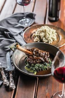 Gebratene oder confierte lammkeule in pfanne mit spinat und rotwein.