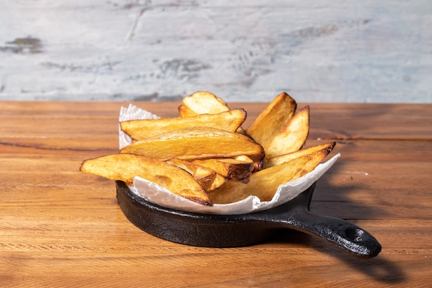 Gebratene oder gebackene kartoffeln in einer schwarzen eisenpfanne auf holztisch.