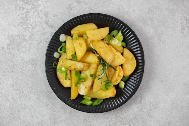 Gebratene ofenkartoffeln auf einem schwarzen teller mit frischen frühlingszwiebeln und rosmarin.