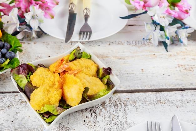 Gebratene panierte garnelen mit grünem salat und tischset.