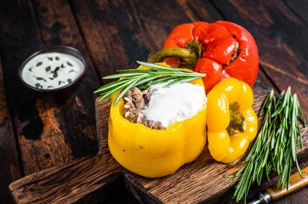 Gebratene paprika gefüllt mit rindfleisch, reis und gemüse auf einem holzbrett