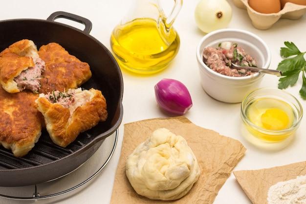 Gebratene pasteten mit fleisch in der pfanne. roher teig auf papier. olivenöl flasche. zwiebelkopf und eigelb in einer schüssel. weißer hintergrund. ansicht von oben