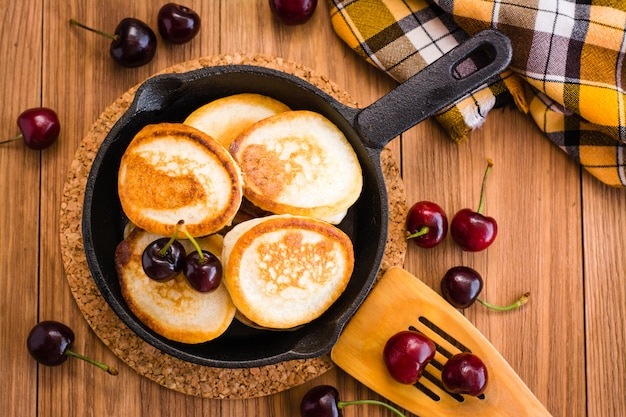 Gebratene pfannkuchen in einer eisenwanne und in reifen kirschen auf einem holztisch. ansicht von oben