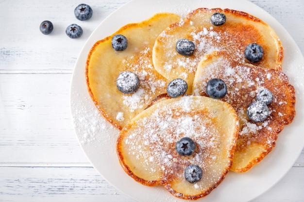 Gebratene pfannkuchen mit frischen blaubeeren mit puderzucker auf einem teller, nahaufnahme, draufsicht