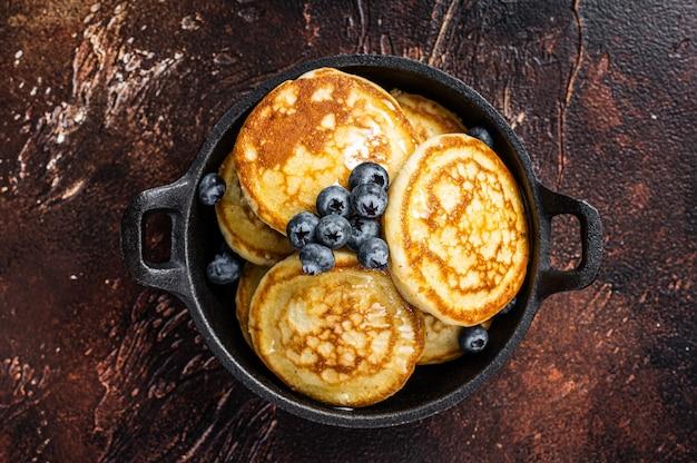 Gebratene pfannkuchen mit frischen blaubeeren und ahornsirup in einer pfanne. draufsicht.