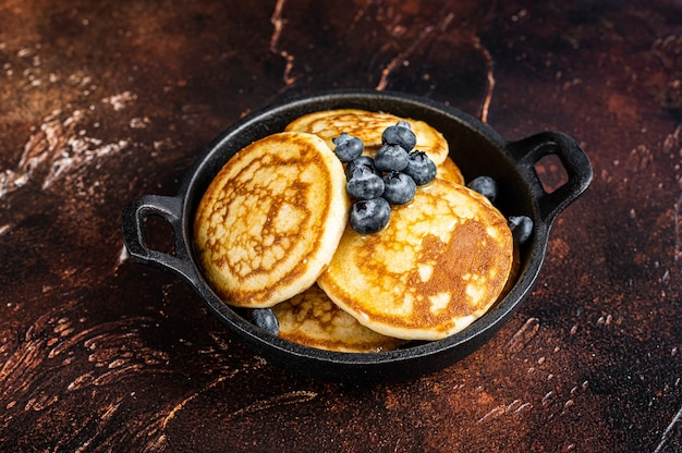 Gebratene pfannkuchen mit frischen blaubeeren und ahornsirup in einer pfanne