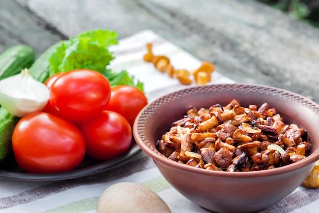Gebratene pfifferlinge mit zwiebel in der rustikalen schüssel und platte mit frischgemüse für salat auf hintergrund