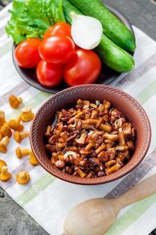Gebratene pfifferlinge mit zwiebel in der rustikalen schüssel und platte mit frischgemüse für salat