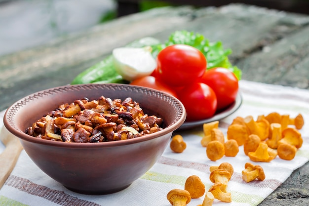 Gebratene pfifferlinge mit zwiebeln in einer rustikalen schüssel und teller mit frischem gemüse für salat auf der oberfläche