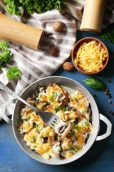 Gebratene pilze, hähnchen-käse-gratin in der pfanne auf farbigem holztisch