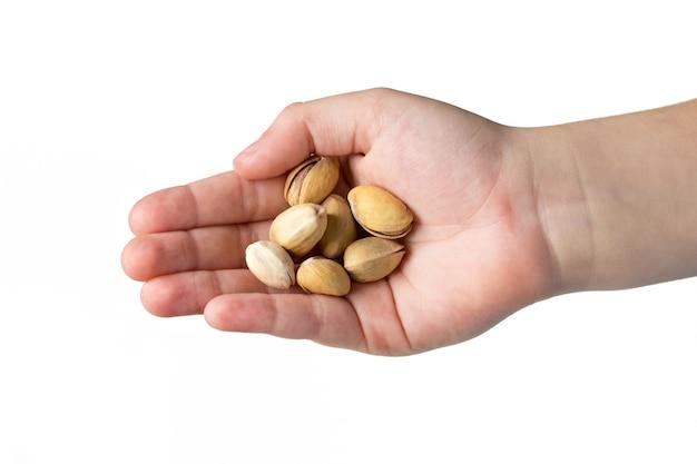 Gebratene pistazien in den händen des kindes lokalisiert auf weißem hintergrund.