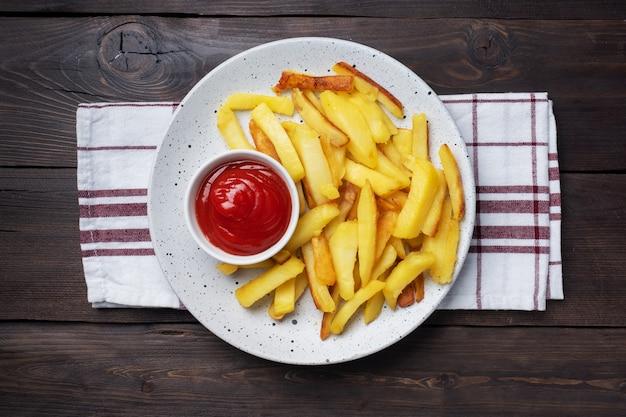 Gebratene pommes-kartoffeln mit tomaten-ketchup-sauce auf einem teller. holztisch. speicherplatz kopieren.