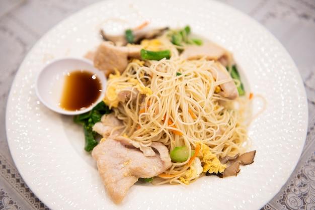 Gebratene reisnudeln mit schweinefleisch und chinesischem grünkohl, gekochten nudeln, schweinefleischgemüse und sauce umrühren