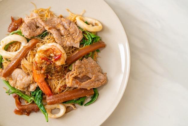 Gebratene reisnudeln und wassermimose mit mischfleisch - asiatische küche