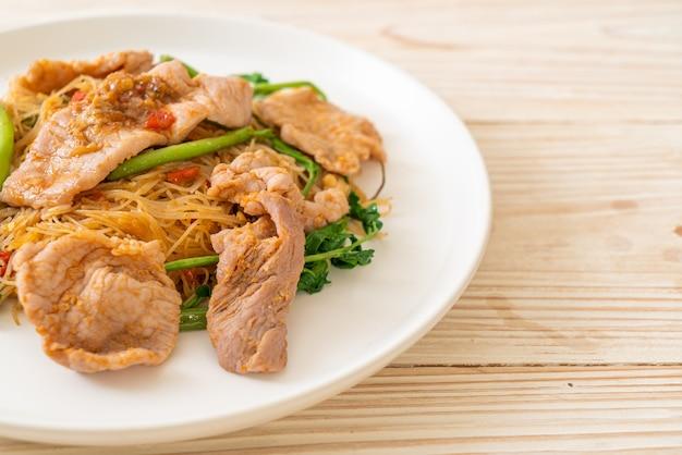 Gebratene reisnudeln und wassermimose mit schweinefleisch - asiatische küche