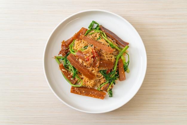 Gebratene reisnudeln und wassermimosen mit eingelegtem tintenfisch - asiatische küche