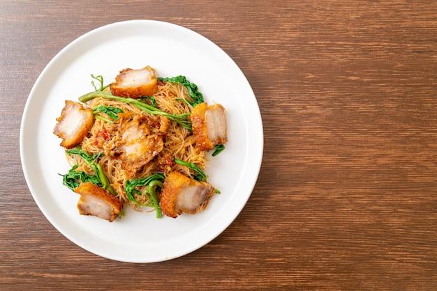 Gebratene reisnudeln und wassermimosen mit knusprigem schweinebauch - asiatische küche