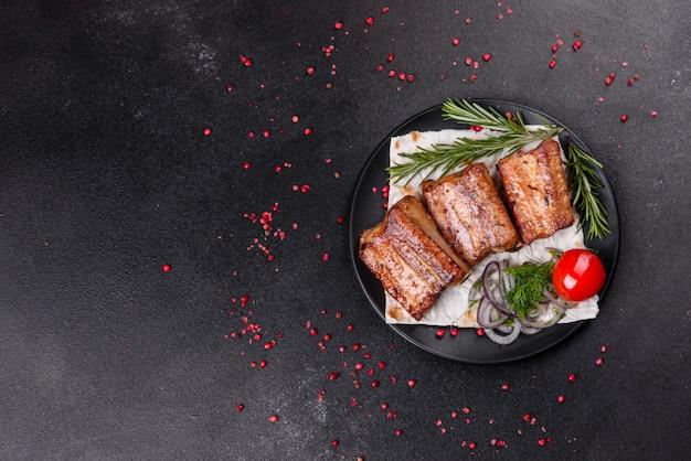 Gebratene rippen mit rosmarin, zwiebel, sauce auf einer betonoberfläche. dunkler tisch. platz für text, copyspace