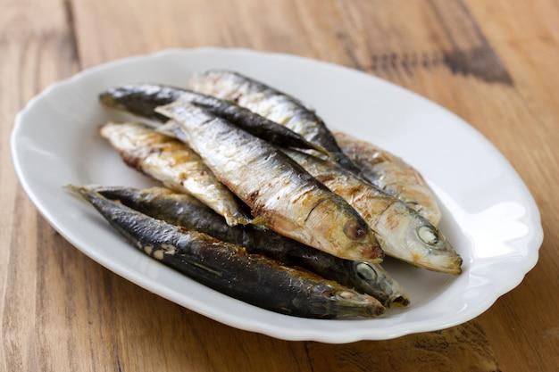 Gebratene sardinen auf weißem teller auf brauner holzoberfläche